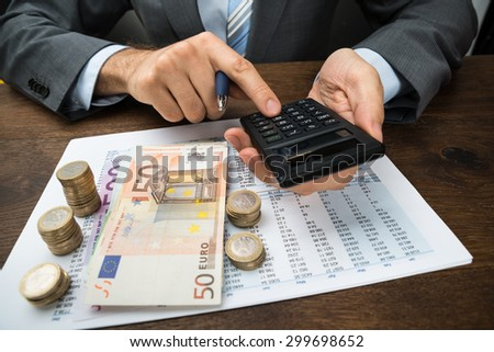 Close-up Of Businessperson Calculating Finance With Money On Desk - stock photo