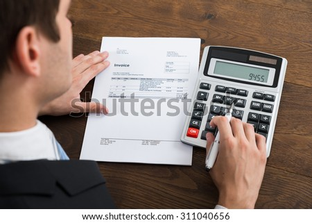 Close-up Of Businessperson Calculating Tax With Calculator In Office - stock photo