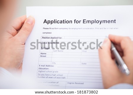 Close-up Of Businessperson Filling An Employment Form - stock photo