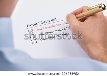 Close-up Of Businessperson Filling Audit Checklist Form Paper - stock photo