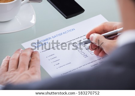Close-up Of Businessperson Filling Survey Form With Pen - stock photo