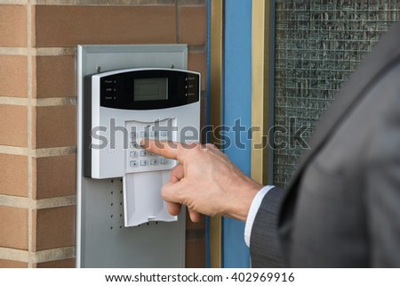 Close-up Of Businessperson Hand Entering Code In Security System - stock photo