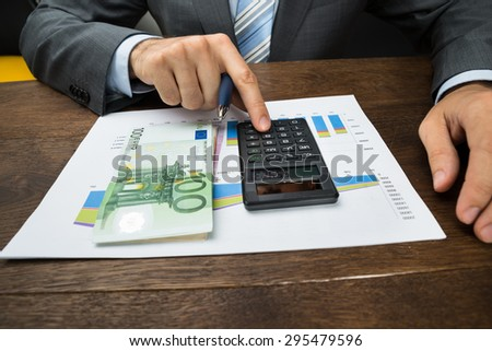 Close-up Of Businessperson Hands Analyzing Graph With Calculator In Office - stock photo