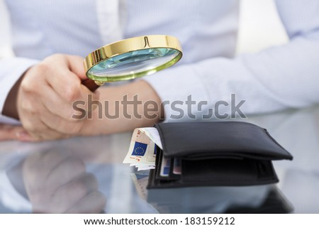 Close-up Of Businessperson Holding Magnifier Over  Money Wallet - stock photo