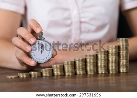 Close-up Of Businessperson Holding Stopwatch With Stack Of Coins At Desk - stock photo