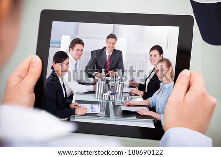 Close-up Of Businessperson Looking At Video Conference On Digital Tablet - stock photo
