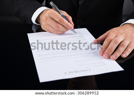 Close-up Of Businessperson Signing Contract Paper With Pen - stock photo