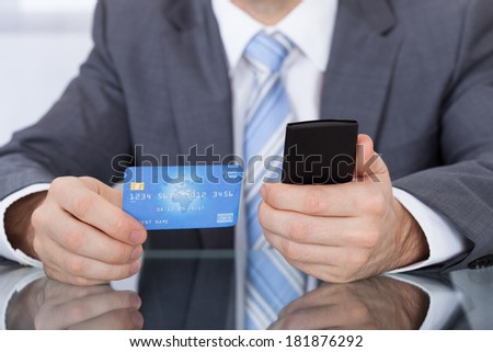 Close-up Of Businessperson Using Phone Card Sitting At Desk - stock photo