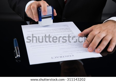 Close-up Of Businessperson Using Stamper Over Contract Paper