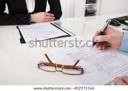 Close-up Of Businessperson With Resume And Pen In Office - stock photo