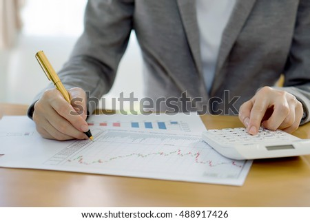 Close-up Of Businesswoman Analyzing Financial Report With Calculator At Wooden