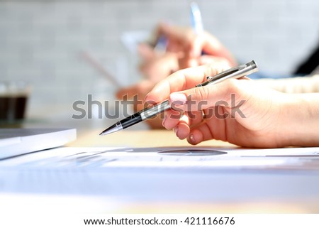 Close-up Of Businesswoman Analyzing Graph with colleagues