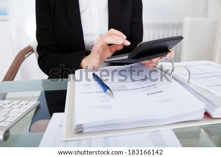 Close-up Of Businesswoman Calculating Bills Using Calculator - stock photo