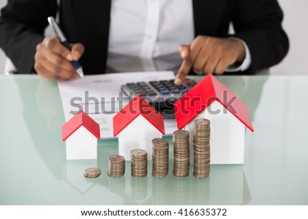 Close-up Of Businesswoman Calculating Invoice With Stacked Coins And House Models On Desk - stock photo