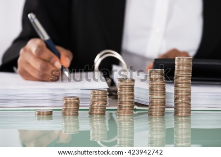 Close-up Of Businesswoman Calculating Tax With Stack Of Coins On Desk - stock photo