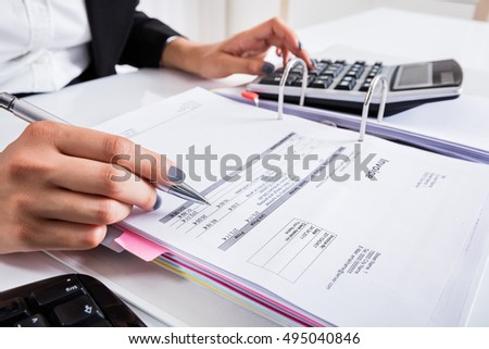 Close-up Of Businesswoman Hand Calculating Invoice Using Calculator At Desk In Office