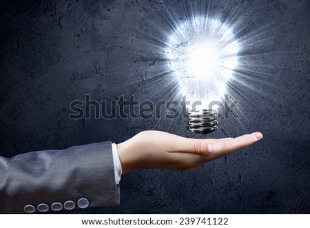 Close up of businesswoman hand holding bulb in palm - stock photo