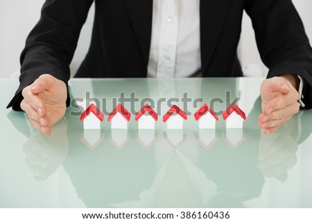 Close-up Of Businesswoman Hand Protecting House Models - stock photo