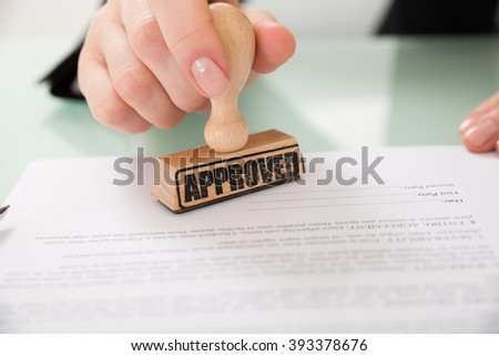 Close-up Of Businesswoman Hand Stamping Approved On Contract Paper