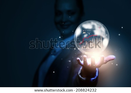 Close up of businesswoman holding bubble with graphs in hand