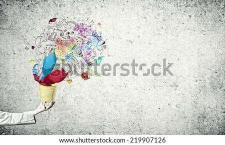 Close up of businesswoman holding bucket with paint splashes - stock photo