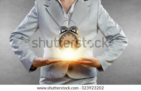 Close up of businesswoman holding in hands alarm clock - stock photo