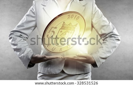 Close up of businesswoman holding in palms euro coin
