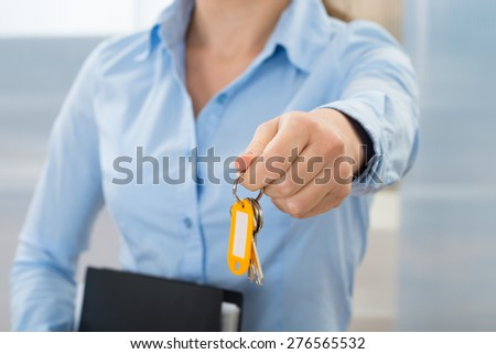 Close-up Of Businesswoman Holding Key With Folder - stock photo