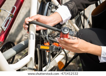 Close-up Of Businesswoman's Hand Locking Up Her Bicycle