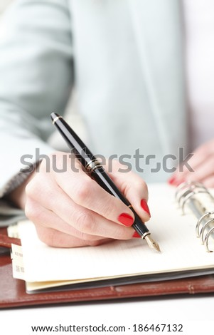 Close-up of businesswoman's hand while making paperwork. Small business. - stock photo