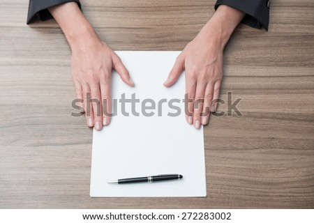 Close up of businesswoman's hands on the desk with the blank paper. Legal contract negotiation. - stock photo