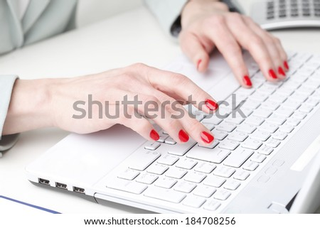 Close-up of businesswoman sitting at desk while working on laptop in office.  Small business. - stock photo