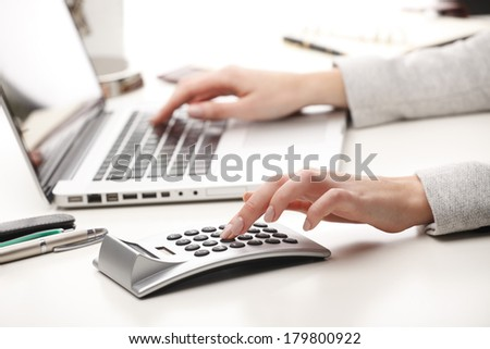 Close-up of businesswoman sitting while working on laptop and calculating.