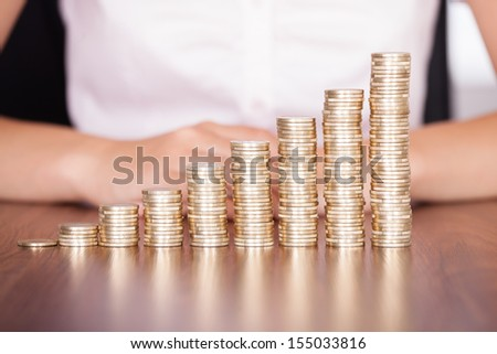 Close-up Of Businesswoman Stacking Gold Coins On Increasing Coins - stock photo