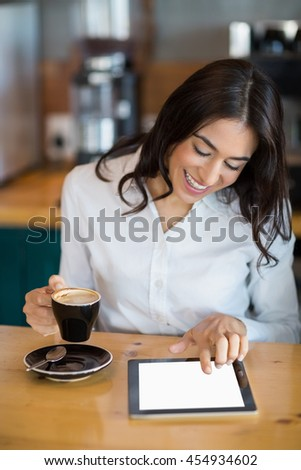 Close-up of businesswoman using digital tablet while having coffee in café - stock photo