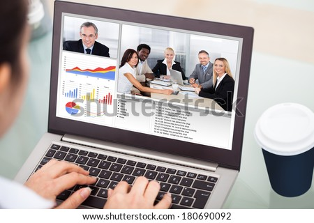 Close-up Of Businesswoman Video Conferencing On Laptop With Disposable Cup - stock photo