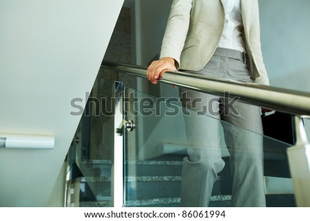 Close-up of businesswoman with briefcase going down the stairway