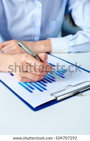 Close-up of businesswoman working with financial document - stock photo