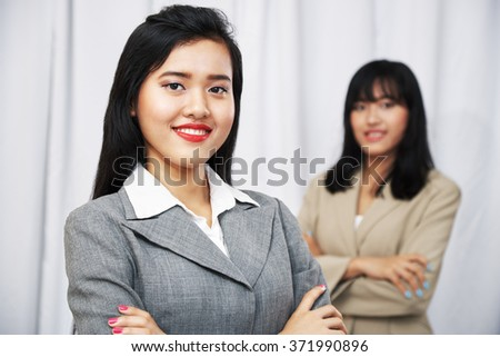 close up of businesswomen wearing suits standing and folding arms