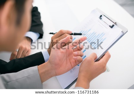 Close-up of busy businessmen analyzing financial results - stock photo