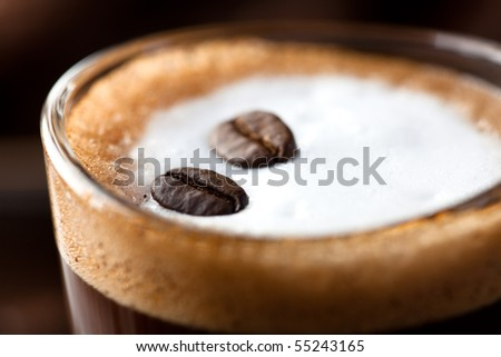 Close up of Caffe Macchiato with coffee beans - stock photo