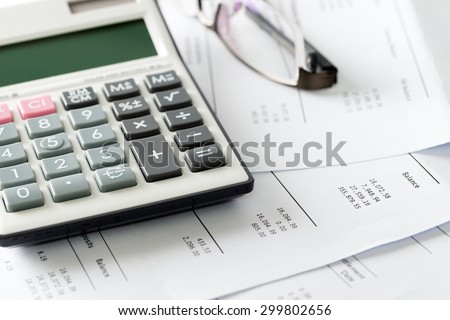 Close up of calculator and glasses on financial budget statement - stock photo