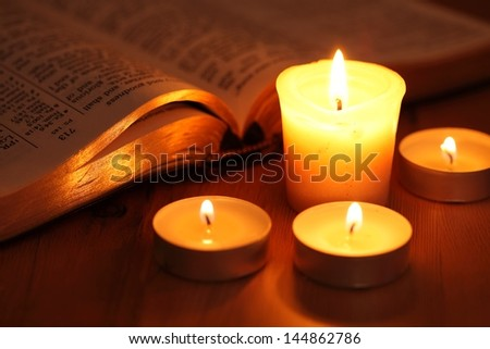 Close-up of candles and open Bible.  - stock photo