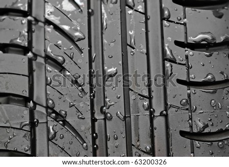 Close-up of car tire with with water drops to background - stock photo