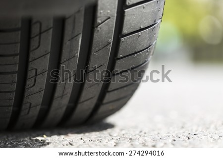 Close up of car tyre tread on the road on a bright day - stock photo