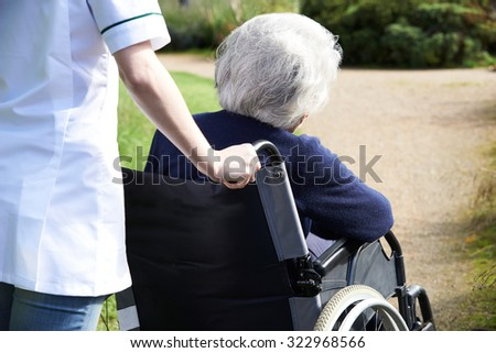 Close Up Of Carer Pushing Senior Woman In Wheelchair - stock photo