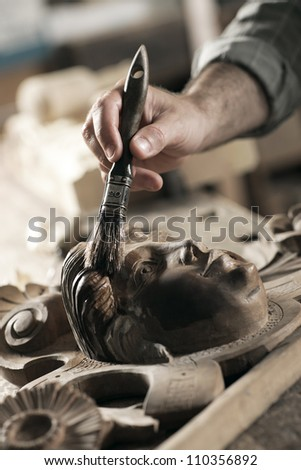 Close Up of carpenter apply varnish to a wooden sculpture - stock photo