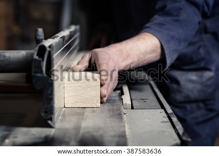 Close up of Carpenter's hands cutting wood with table saw in workshop - stock photo