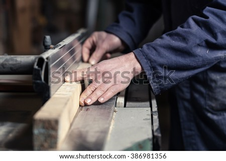 Close up of Carpenter's hands cutting wood with tablesaw in workshop - stock photo