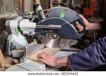 Close up of carpenter's hands using circular saw in his workshop - stock photo